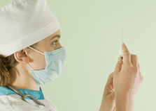 Young lady doctor with syringe. Young lady doctor preparing syringe for injection Royalty Free Stock Photography