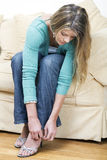 Young lady doing up her shoes. Sitting on a sofa stock photos
