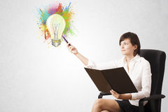 Young lady drawing a colorful light bulb with colorful splashes Stock Images