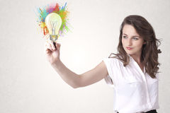 Young lady drawing a colorful light bulb with colorful splashes Royalty Free Stock Images