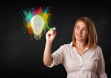 Young lady drawing a colorful light bulb with colorful splashes Royalty Free Stock Photos