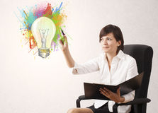 Young lady drawing a colorful light bulb with colorful splashes Stock Image