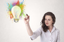 Young lady drawing a colorful light bulb with colorful splashes Royalty Free Stock Photo