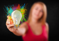 Young lady drawing a colorful light bulb with colorful splashes Royalty Free Stock Photography