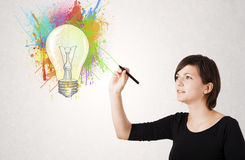 Young lady drawing a colorful light bulb with colorful splashes Stock Photography