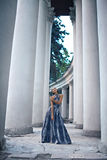 Young lady in dress at the entrance of neoclassical building Royalty Free Stock Photo