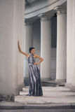 Young lady in dress at the entrance of neoclassical building Royalty Free Stock Image
