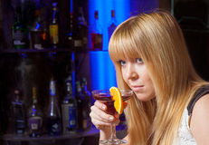 Young lady drinking alone in the club Royalty Free Stock Images