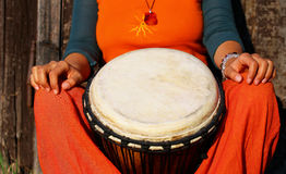 Young lady drummer with her djembe drum on rustic wooden door background Royalty Free Stock Photography