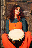 Young lady drummer with her djembe drum on rustic wooden door background Royalty Free Stock Images