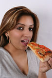 Young lady eating pizza. A studio portrait of an attractive Asian woman with hungry facial expression eating a slice of pizza and watching Royalty Free Stock Photos
