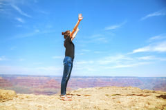 Young lady at the edge of the Grand Canyon rim Royalty Free Stock Images