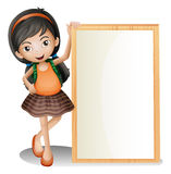 A young lady beside an empty signboard Stock Photography