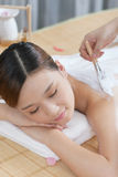 A young lady enjoy body mask in spa salon Stock Photos
