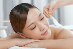 A young lady enjoy body mask in spa salon. Indoors Royalty Free Stock Photography