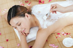 A young lady enjoy body mask in spa salon. Indoors Stock Image