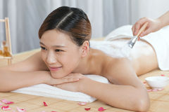 A young lady enjoy body mask in spa salon. Indoors Stock Photo
