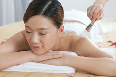 A young lady enjoy body mask in spa salon. Indoors Stock Photography