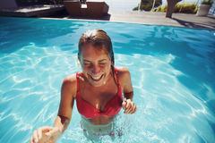 Young lady enjoying herself in swimming pool Stock Photo