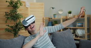 Young lady enjoying new experience with augmented reality glasses laughing. Young lady is enjoying new experience with augmented reality glasses sitting on sofa stock video footage