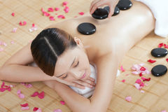 A young lady enjoying stone massage at spa. At beauty salon, indoors Royalty Free Stock Photo