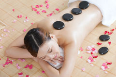 A young lady enjoying stone massage at spa. At beauty salon, indoors Royalty Free Stock Photography