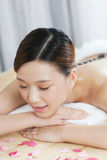 A young lady enjoying stone massage at spa. At beauty salon, indoors Stock Photography