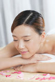 A young lady enjoying stone massage at spa. At beauty salon, indoors Stock Photo