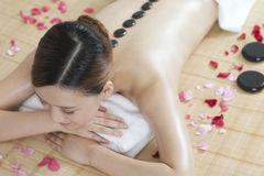A young lady enjoying stone massage at spa. At beauty salon, indoors Royalty Free Stock Image