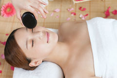 A young lady enjoying stone massage at spa. At beauty salon, indoors Stock Photos