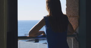 Young lady enjoying the sun on the balcony of her hotel room. View from behind, with blue skies and sea in the background stock video footage