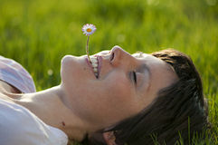Young lady with flower in her mouth. Relaxing in springtime royalty free stock photography