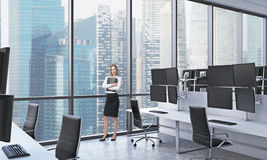A young lady in formal clothes holds a black document folder in the modern panoramic office in Singapore. White tables equipped wi Royalty Free Stock Images