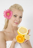Young lady with fruits and pink flower in hair. On isolated studio pictures Royalty Free Stock Photos