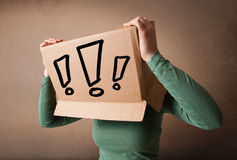 Young lady gesturing with a cardboard box on her head with excla Stock Photos