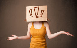 Young lady gesturing with a cardboard box on her head with excla Stock Photography