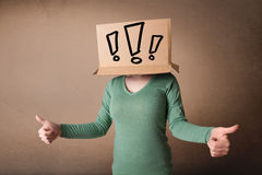 Young lady gesturing with a cardboard box on her head with excla Royalty Free Stock Images