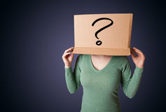 Young lady gesturing with a cardboard box on her head with quest Stock Photo