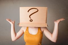 Young lady gesturing with a cardboard box on her head with quest Royalty Free Stock Photography