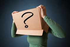 Young lady gesturing with a cardboard box on her head with quest Stock Photos