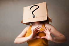 Young lady gesturing with a cardboard box on her head with quest Stock Photography