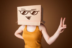 Young lady gesturing with a cardboard box on her head with smile Royalty Free Stock Photo