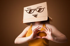 Young lady gesturing with a cardboard box on her head with smile. Young lady standing and gesturing with a cardboard box on her head with smiley face Stock Image