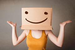 Young lady gesturing with a cardboard box on her head with smile Stock Photography