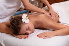 Young lady getting back massage. At a spa Royalty Free Stock Photos