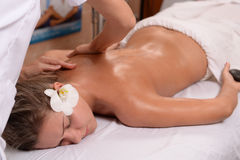 Young lady getting back massage. At a spa Royalty Free Stock Photo