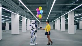 Young lady is giving balloons to a human-like cyborg stock footage