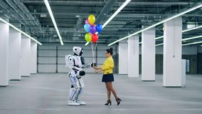 Young lady is giving colourful balloons to a robot stock video
