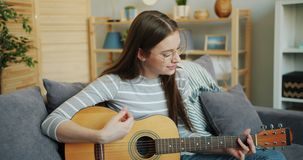 Young lady in glasses playing the guitar at home enjoying music and leisure time. Attractive young lady in glasses is playing the guitar at home enjoying music stock video footage