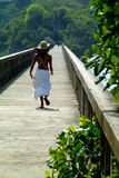 Young lady is goaway, walking on a bridge. Young dominican lady is goaway, walking on a bridge,  wearing a white skirt and a beige hat Stock Images